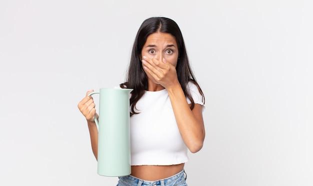 Jonge spaanse vrouw die de mond bedekt met handen met een geschokte en een koffiethermos