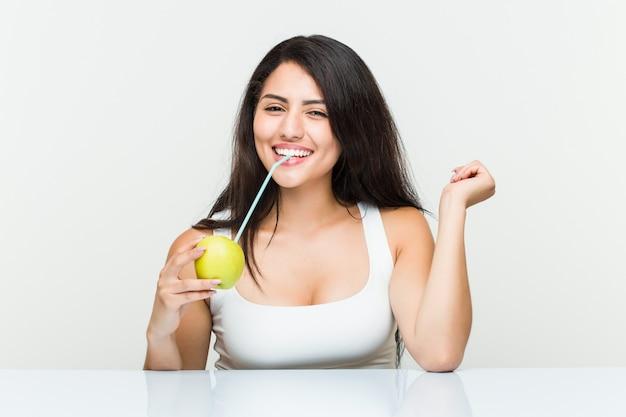 Jonge spaanse vrouw die een appelsap met een stro drinkt