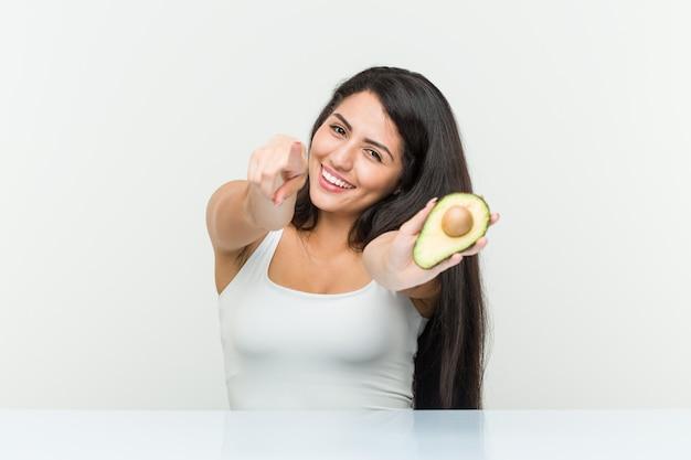 Jonge spaanse vrouw die een avocado vrolijke glimlachen houdt richtend aan voorzijde.