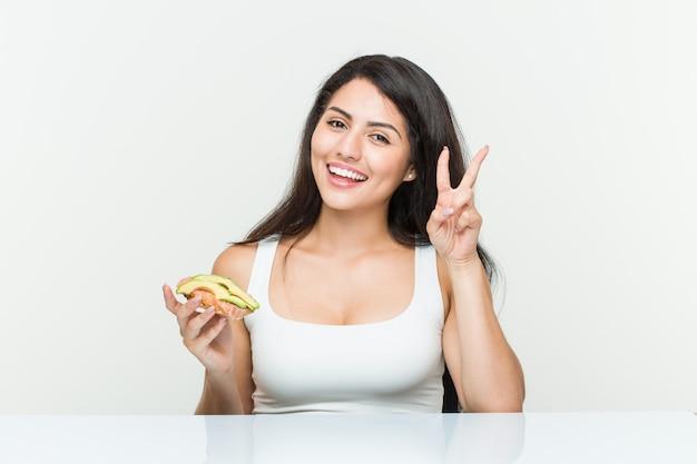 Jonge spaanse vrouw die een avocadotoost houden die overwinningsteken tonen en breed glimlachen.