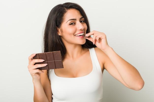 Jonge spaanse vrouw die een chocoladetablet houdt