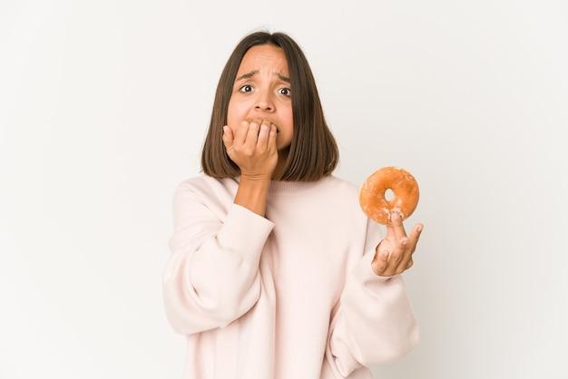 Jonge spaanse vrouw die een doughnut eet die vingernagels bijt, zenuwachtig en zeer angstig.