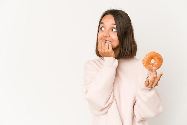 Jonge spaanse vrouw die een doughnut eet ontspannen denkend aan iets dat een exemplaarruimte bekijkt.