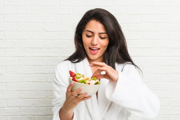 Jonge spaanse vrouw die een fruitkom op het bed eet