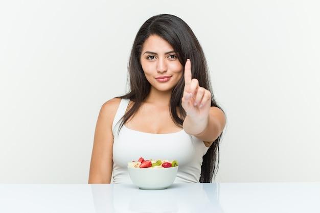 Jonge spaanse vrouw die een fruitschaal eet die nummer één met vinger toont.