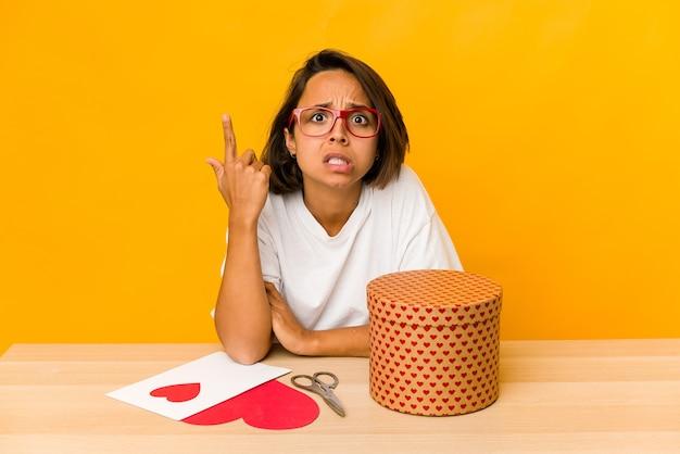 Jonge spaanse vrouw die een geïsoleerde valentijnskaartgift voorbereidt die een teleurstellinggebaar met wijsvinger toont.