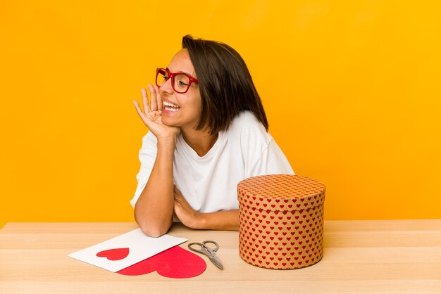 Jonge spaanse vrouw die een geïsoleerde valentijnskaartgift voorbereidt die en palm dichtbij geopende mond houdt.