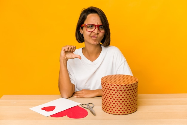Jonge spaanse vrouw die een geïsoleerde valentijnskaartgift voorbereidt met een afkeergebaar, duimen naar beneden. meningsverschil concept.