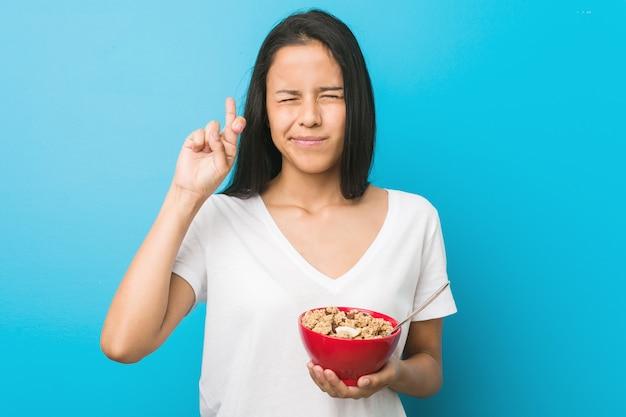 Jonge spaanse vrouw die een graangewassenkom houdt die vingers kruist voor het hebben van geluk