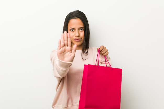 Jonge spaanse vrouw die een het winkelen zak houdt die zich met uitgestrekte hand bevindt die eindeteken toont