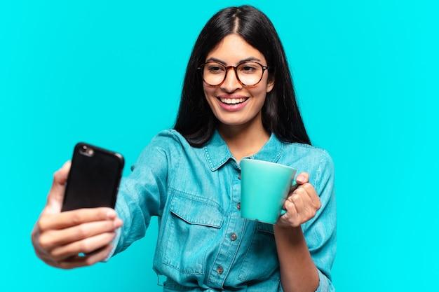 Jonge spaanse vrouw die een koffie heeft