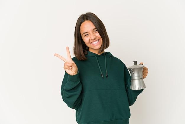 Jonge spaanse vrouw die een koffiezetapparaat blij en zorgeloos houdt die een vredessymbool met vingers tonen.