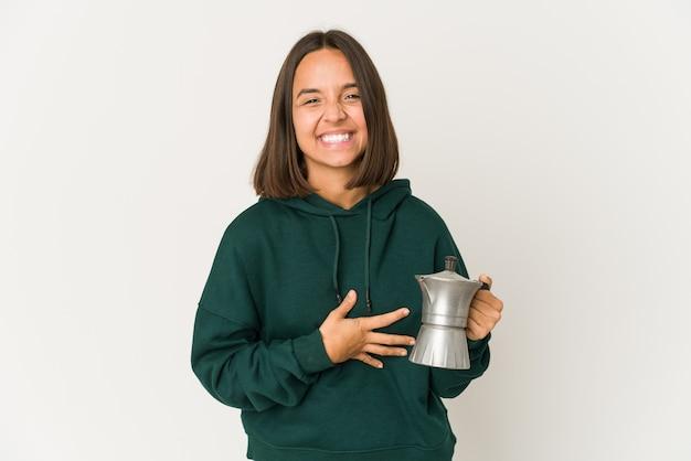 Jonge spaanse vrouw die een koffiezetapparaat houdt dat en pret lacht heeft.