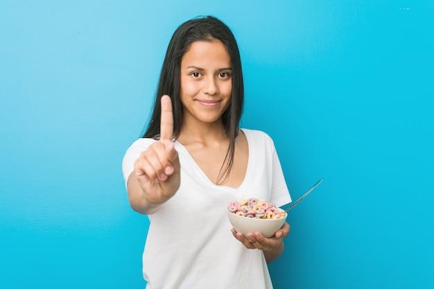 Jonge spaanse vrouw die een kom van het suikergraangewas houdt die nummer één met vinger toont.