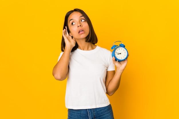 Jonge spaanse vrouw die een megafoon houdt die een roddel probeert te luisteren.