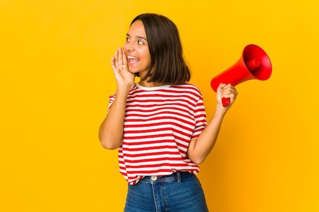 Jonge spaanse vrouw die een megafoon houdt die en palm dichtbij geopende mond houdt