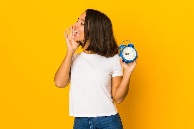 Jonge spaanse vrouw die een megafoon vasthoudt die schreeuwt en palm in de buurt van geopende mond houdt.