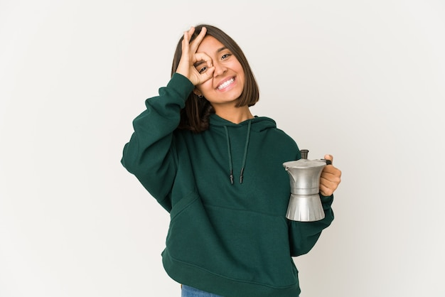 Jonge spaanse vrouw die een opgewonden koffiezetapparaat houdt die ok gebaar op oog houdt.