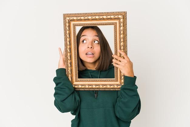 Jonge spaanse vrouw die een oud frame houdt dat probeert een roddel te luisteren.