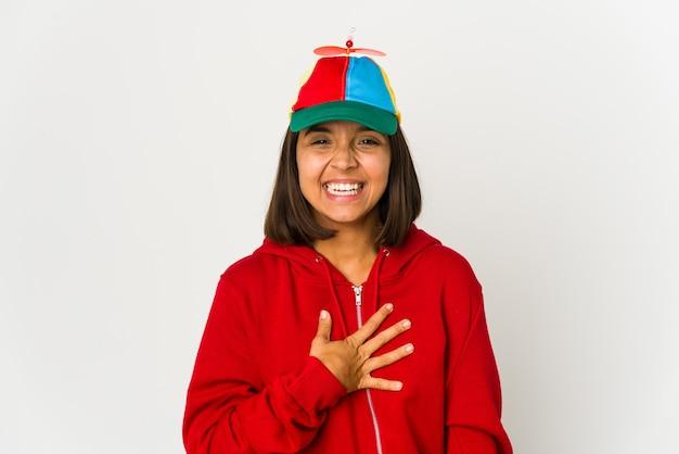 Jonge spaanse vrouw die een pet met geïsoleerde propeller draagt, lacht hardop terwijl ze de hand op de borst houdt.
