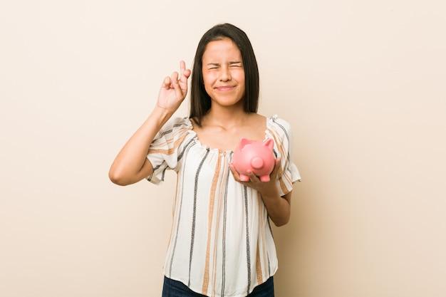 Jonge spaanse vrouw die een spaarvarken houdt dat vingers kruist voor het hebben van geluk