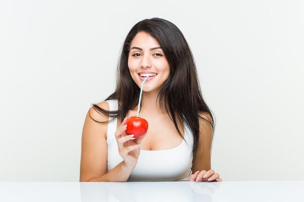 Jonge spaanse vrouw die een tomatesap met een stro drinkt