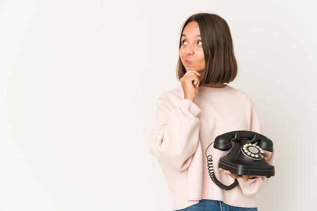 Jonge spaanse vrouw die een vintage telefoon houdt die zijdelings met twijfelachtige en sceptische uitdrukking kijkt.