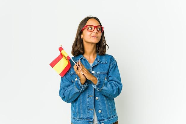 Jonge spaanse vrouw die een vlag houdt die op witte achtergrond wordt geïsoleerd die het opzetten van een plan in mening, het opzetten van een idee.