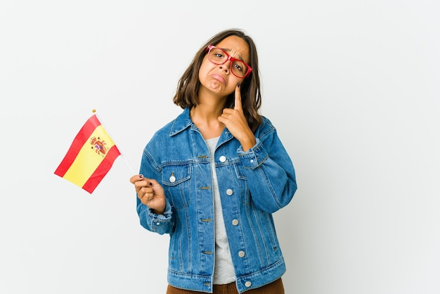 Jonge spaanse vrouw die een vlag houdt die op witte achtergrond wordt geïsoleerd huilen, ongelukkig met iets, ondraaglijke pijn en verwarringconcept.