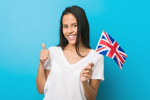 Jonge spaanse vrouw die een vlag houdt die van het verenigd koninkrijk en duim glimlacht opheft