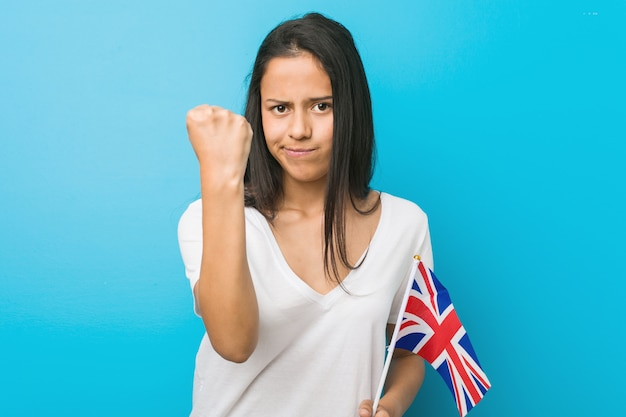 Jonge spaanse vrouw die een vlag houdt die van het verenigd koninkrijk vuist toont aan camera, agressieve gelaatsuitdrukking.