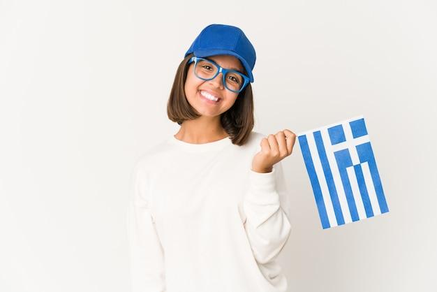 Jonge spaanse vrouw die een vlag van griekenland gelukkig, glimlachend en vrolijk houdt