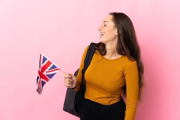 Jonge spaanse vrouw die een vlag van het verenigd koninkrijk houdt die in zijpositie lacht