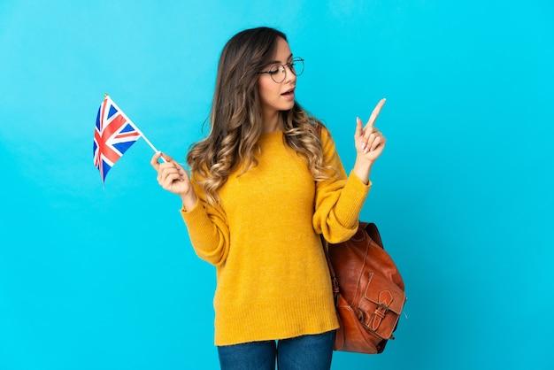 Jonge spaanse vrouw die een vlag van het verenigd koninkrijk houdt die op blauwe muur wordt geïsoleerd die een idee denkt dat de vinger omhoog richt