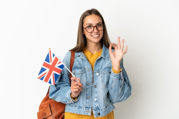 Jonge spaanse vrouw die een vlag van het verenigd koninkrijk houdt over geïsoleerde witte achtergrond die ok teken met vingers toont