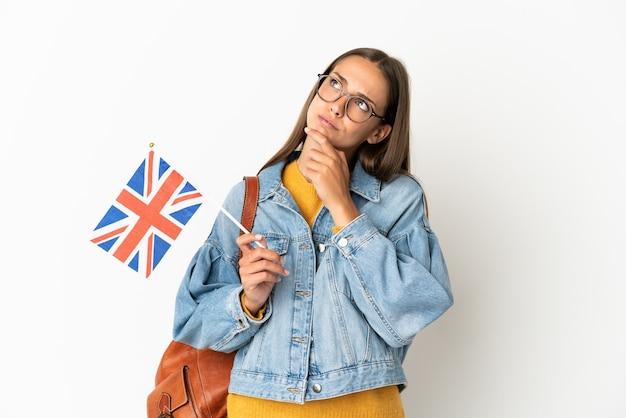 Jonge spaanse vrouw die een vlag van het verenigd koninkrijk houdt over geïsoleerde witte achtergrond die twijfels heeft