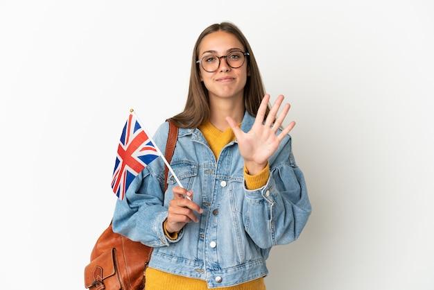 Jonge spaanse vrouw die een vlag van het verenigd koninkrijk houdt over geïsoleerde witte achtergrond die vijf met vingers telt