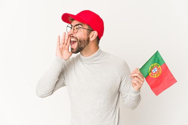 Jonge spaanse vrouw die een vlag van portugal houdt die schreeuwt en palm dichtbij geopende mond houdt