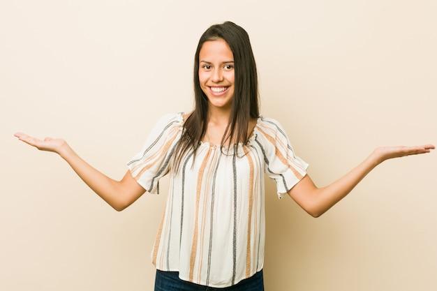 Jonge spaanse vrouw die een welkome uitdrukking toont.