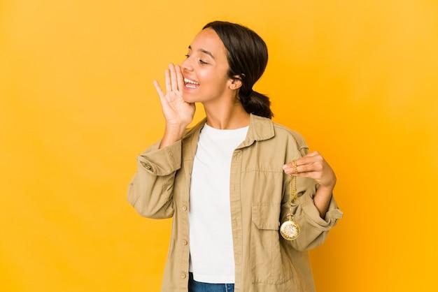 Jonge spaanse vrouw die een zakhorloge houdt en palm dichtbij geopende mond houdt.