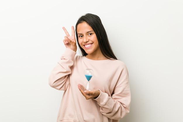 Jonge spaanse vrouw die een zandloper houdt die overwinningsteken toont en breed glimlacht.