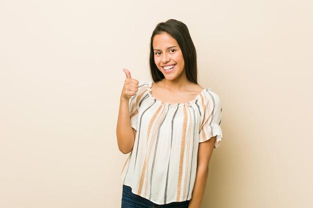 Jonge spaanse vrouw die en duim glimlacht opheft