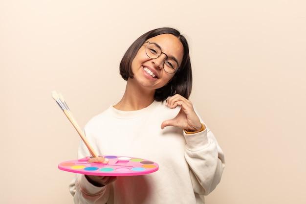 Jonge spaanse vrouw die en gelukkig, leuk, romantisch en verliefd glimlacht voelt en hartvorm met beide handen maakt