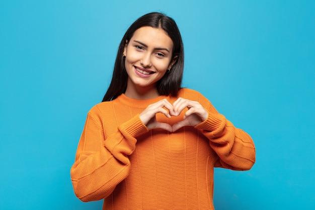 Jonge spaanse vrouw die en gelukkig, leuk, romantisch en verliefd glimlacht voelt, hartvorm makend met beide handen
