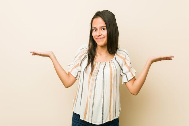 Jonge spaanse vrouw die en schouders in het vragen van gebaar twijfelen ophalen.