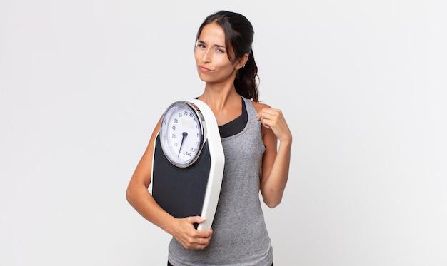 Jonge spaanse vrouw die er arrogant, succesvol, positief en trots uitziet en een weegschaal vasthoudt. dieet concept