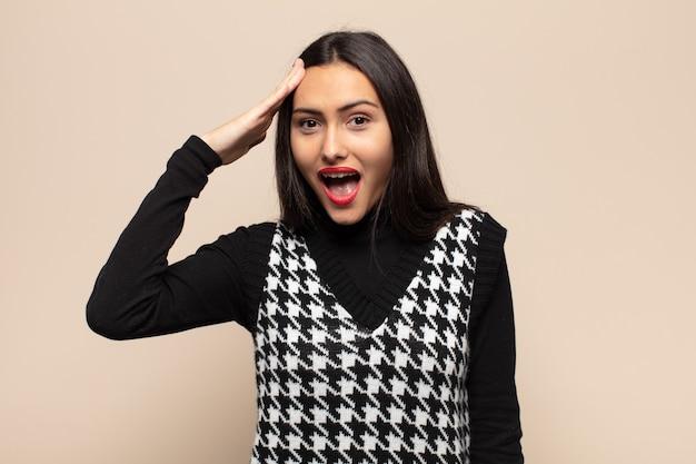 Jonge spaanse vrouw die er blij, verbaasd en verrast uitzag, lachte en zich verbluffend en ongelooflijk goed nieuws realiseerde