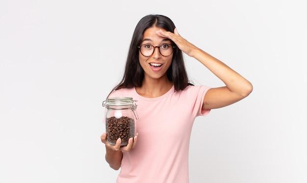 Jonge spaanse vrouw die er blij, verbaasd en verrast uitziet en een fles koffiebonen vasthoudt