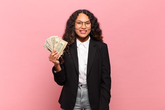 Jonge spaanse vrouw die er gelukkig en aangenaam verrast uitziet, opgewonden met een gefascineerde en geschokte uitdrukking. dollar biljetten concept