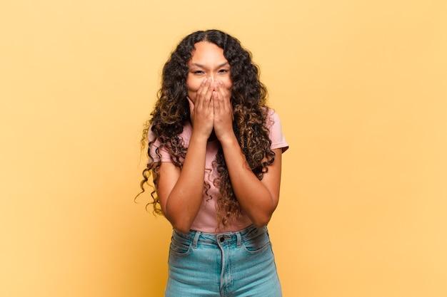 Jonge spaanse vrouw die er gelukkig, vrolijk, gelukkig en verrast uitziet en de mond bedekt met beide handen